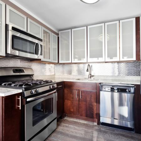Kitcen with stainless dishwasher, over, refrigarator and Microwave.