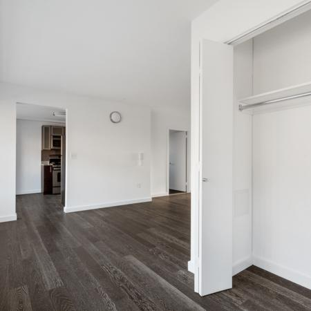 Coat closet in living room with wood like floors