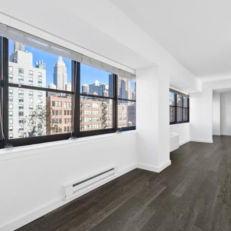 Large window with view of city in hallway off living room