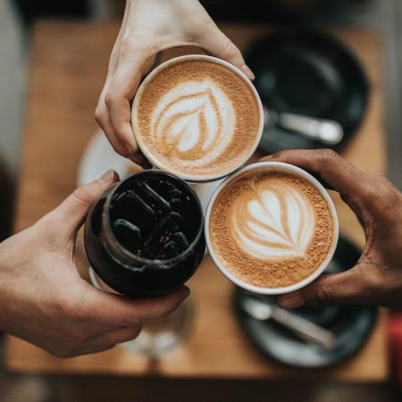 hands holding coffee cups cheersing