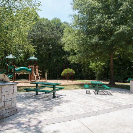 Outdoor grilling area with playground to left