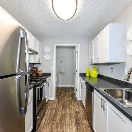 Kitchen with white cabinet uppers and lowers, stainless steel sink, refrigarator and stove