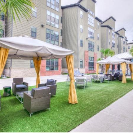 Catalyst, exterior, dining area, tent covered seating, sparkling blue swimming pool, courtyard, brick, green, and tan buildings, pavilion, lounge chairs,