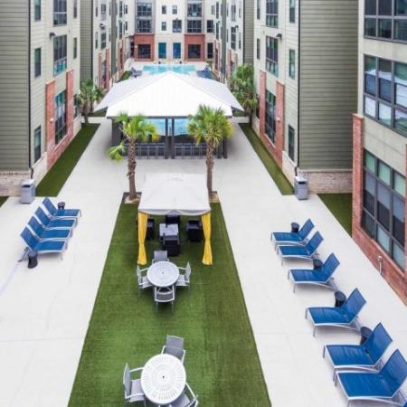 Catalyst, exterior, aerial view, dining area, tent covered grills, sparkling blue swimming pool, courtyard, brick, green, and tan buildings, pavilion, lounge chairs,