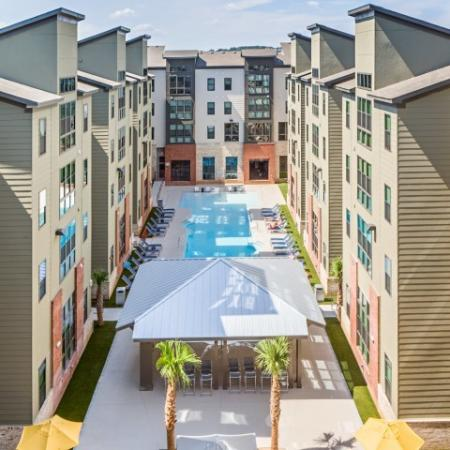 Catalyst, exterior, aerial view, sparkling blue swimming pool, courtyard, brick, green, and tan buildings, pavilion, lounge chairs,