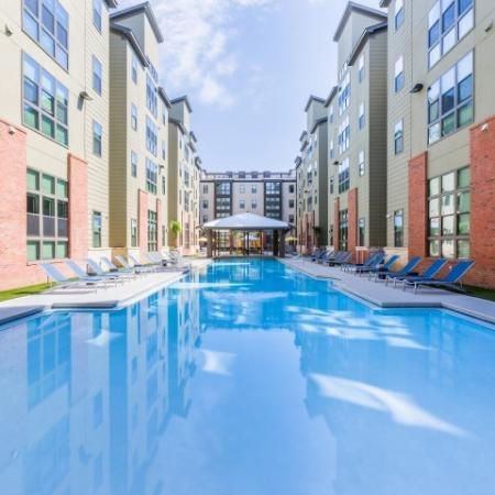 Catalyst, exterior, sparkling blue swimming pool, courtyard, brick, green, and tan buildings, pavilion, lounge chairs,