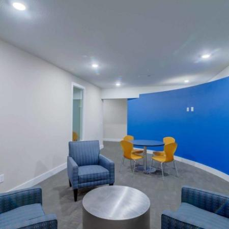 Catalyst, interior, common room, seating area, blue arm chairs, table and orange chairs, blue accent wall