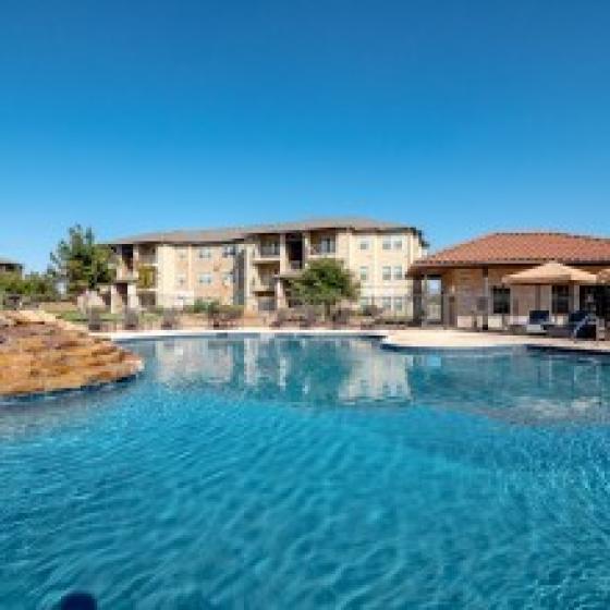 Resort Inspired Swimming pool overlooking property buildings
