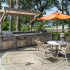Outdoor grill with table and sitting for outdoor dining.