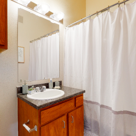 Bathroom with large mirror over vanity | The Edge on Hovey | Apartments in Normal, IL