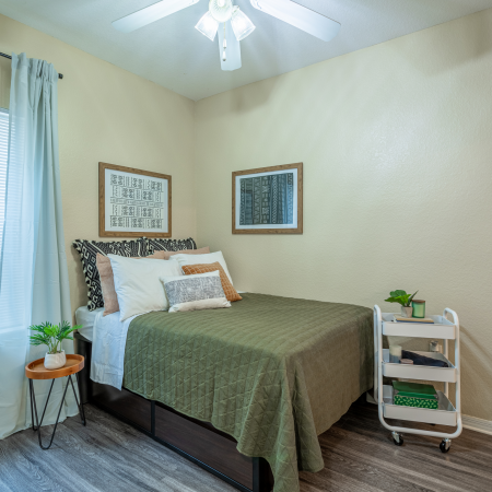 Charming bedroom view | Sizable bed | Draping curtains |  Ceiling fan | Hawks Landing | Apartments in Tampa, FL