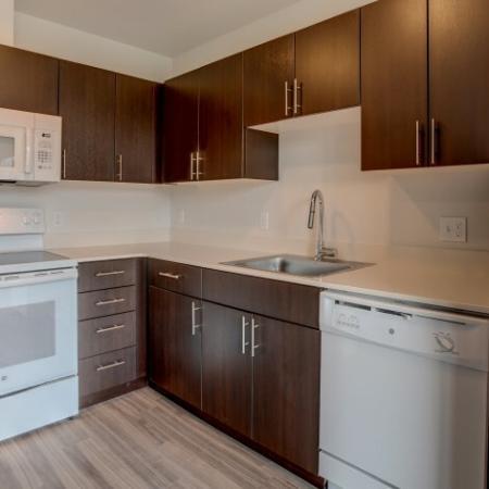 Kitchen with White Appliances & Dark Cabinetry | HANA Apartments | Seattle Studio Apartments