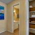 Entrance to bathroom: Closet door with linings, Cream colored walls with white trim.