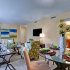 Living room area: Open floor plan dining and living area, Cream colored walls, colorful portraits, well lighted, nice furnishings.