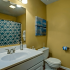 Bathroom Interior: Yellow accent walls, decorative wall art, white standing cabinet with sink. Large toilet, and metal accent pieces, large mirror, nice lighting.