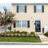 Townhomes for rent in Middle River, MD with yellow siding, shutters, and beautiful landscaping