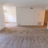 Carpeted living room with glass sliding patio doors at Princeton Orchards Apartments in South Brunswick, NJ.