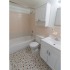 Model bathroom with vanity, toilet and tub shower at Princeton Orchards Apartments in Dayton, NJ.