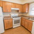 Model kitchen with wood cabinets and modern appliances at Polo Ridge apartments in Burlington, NJ.
