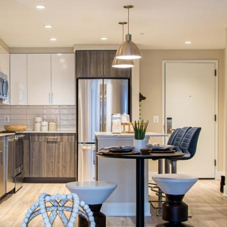 Designer Kitchen with Quartz Counter Tops, Stainless Steel Appliances and Wood-Style Flooring