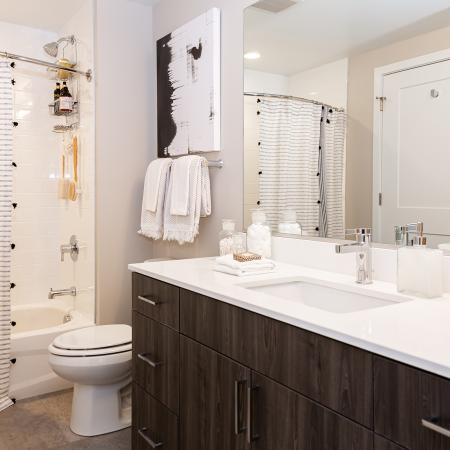 Bathroom with Ceramic Wall Surrounds Tile Flooring, and a Quartz Counter Top.