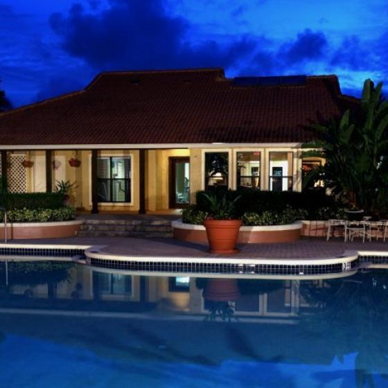 Tuscany Pointe Boca, exterior, night, sparkling blue swimming pool, clubhouse, lounge chairs,