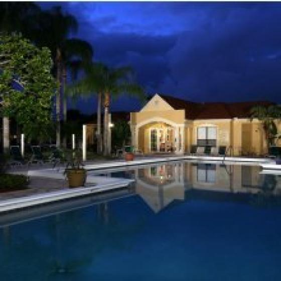 Savannah Place, exterior, night, sparkling blue swimming pool, trees, clubhouse