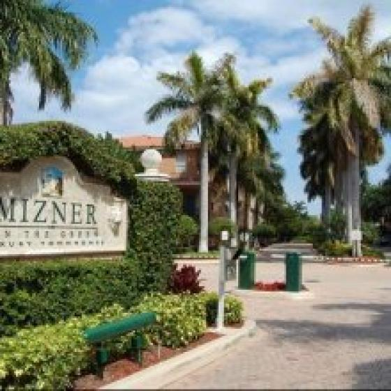 Mizner on the Green Rental- Front entrance view- green area with property logo- road leading to parking lot-palm trees