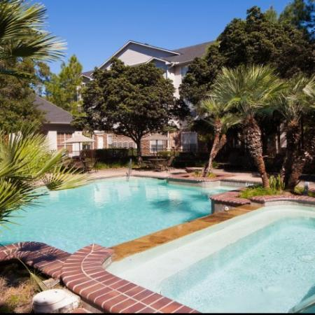 Large swimming pool with spa surrounded by palm trees | Apartment Amenities | Houston, Texas 77043