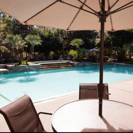 Outdoor lounging is available around the swimming  pool | Apartment Amenities | Houston, Texas 77043