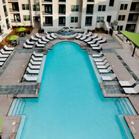 Sparkling Pool surrounded by lounge chairs, tables and umbrellas