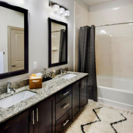 Spacious Master Bathroom with custom maple cabinetry, granite countertops with undermount sinks and curved shower rod