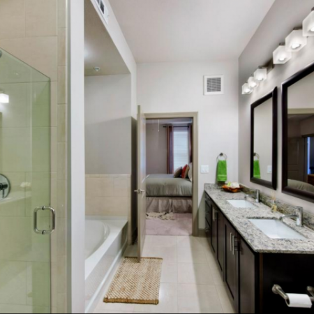 Spacious Master Bathroom with custom maple cabinetry, granite countertops with double undermount sinks and separate shower/tub