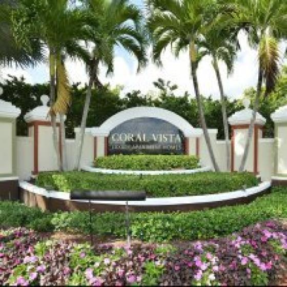 Exterior monument Coral Vista Luxury Apartment Homes sign surrounded by lush landscape