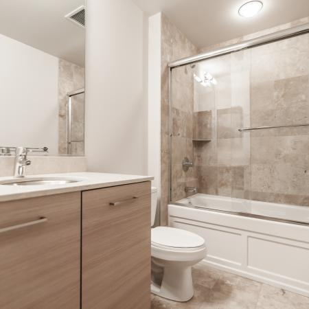 Modern bathroom with a deep soaking tub, designer marble tile and countertop