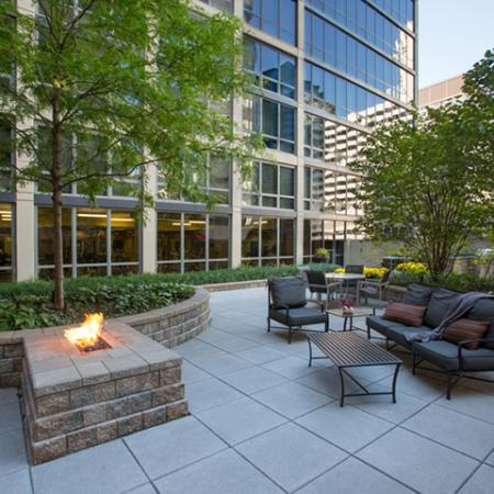 Outdoor lounge and firepit area with trees and tables and chairs