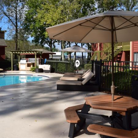 Deerfield Apartments poolside picnic table with umbrella shaded by tree