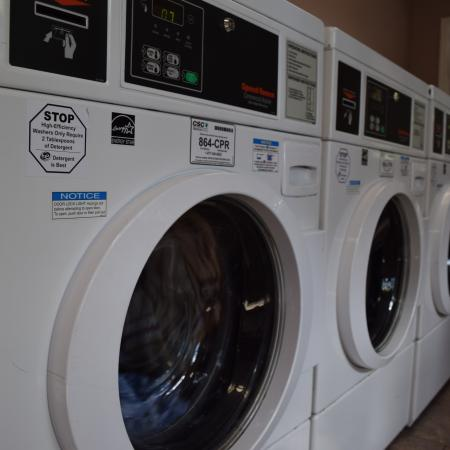 Deerfield Apartments On site laundry facilities with large industrial machinery