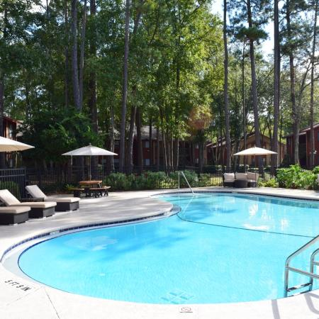 Deerfield Apartments view of pool, deck and lounge areas surrounded by large trees that provide shade