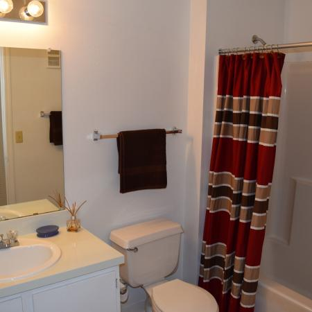 Deerfield Apartments bathroom with tub-shower combo and single sink with Hollywood lights overhead
