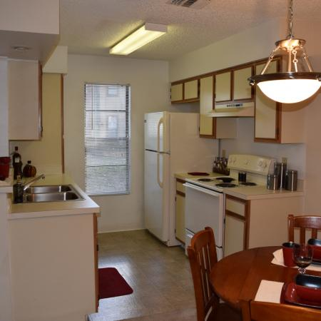 Deerfield Apartments view of dining room with overhead pendant light and kitchen with appliances and a large window