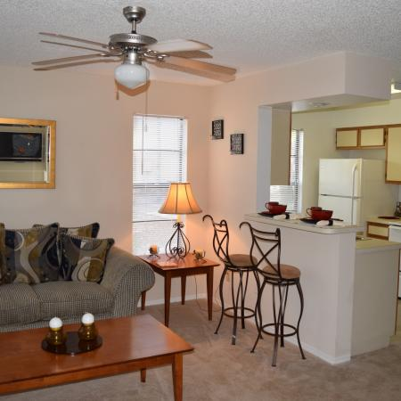 Deerfield Apartments view of living room with ceiling fan and eat in kitchen