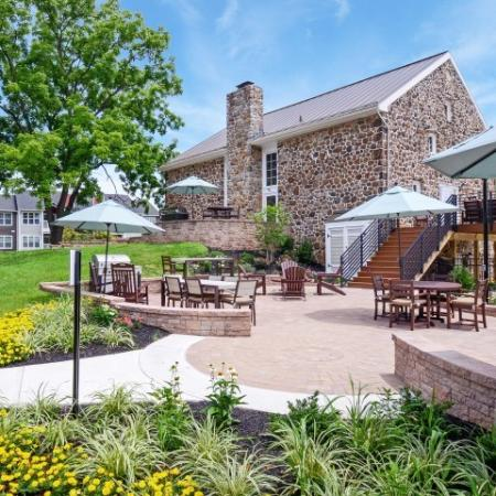 Exterior rear view of clubhouse and grilling area, including tables and patio chairs.