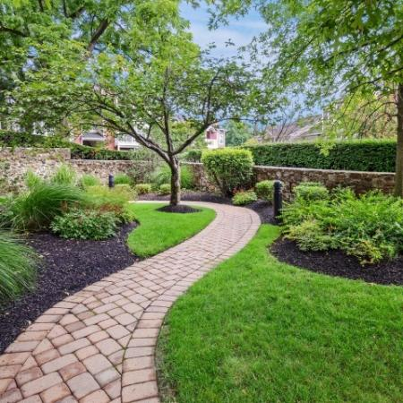Property landscaping, including stone walkway surrounded by trees and foliage.