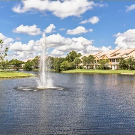 Large pond with fountain, lawn, landscaping and apartment community