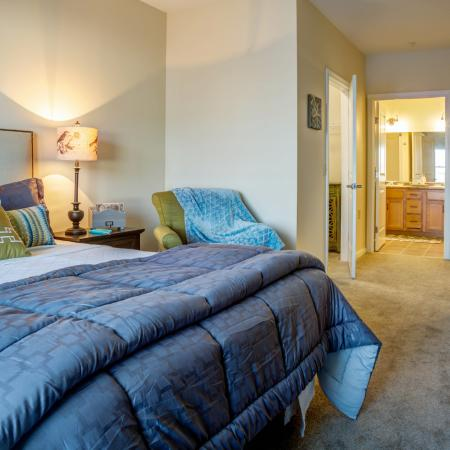 Furnished bedroom with plush carpeting. Bed, nightstand and chair, two dressers, walk-in closet and en suite bathroom situated in large room with lots of natural light.