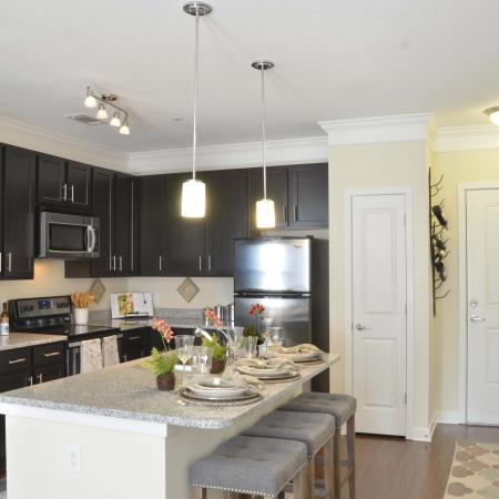 Furnished model kitchen including granite island and stainless appliances
