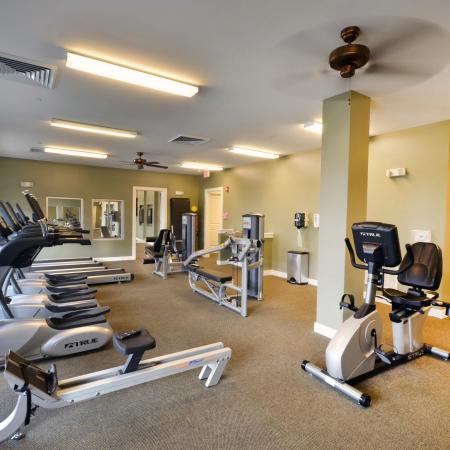 Front room of 24 hr fitness center including rowing machine, elipticals, bikes