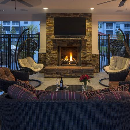 Evening view of seating area and outdoor television under pool cabana with fireplace on