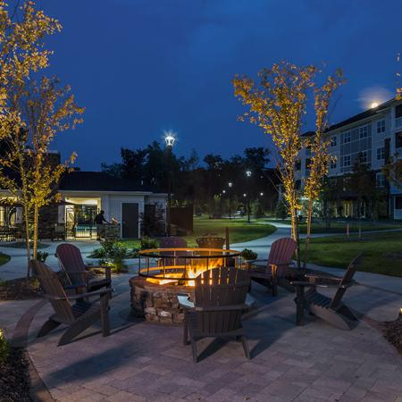 Evening view of gas fire pit and adirondack chairs on backside of village green